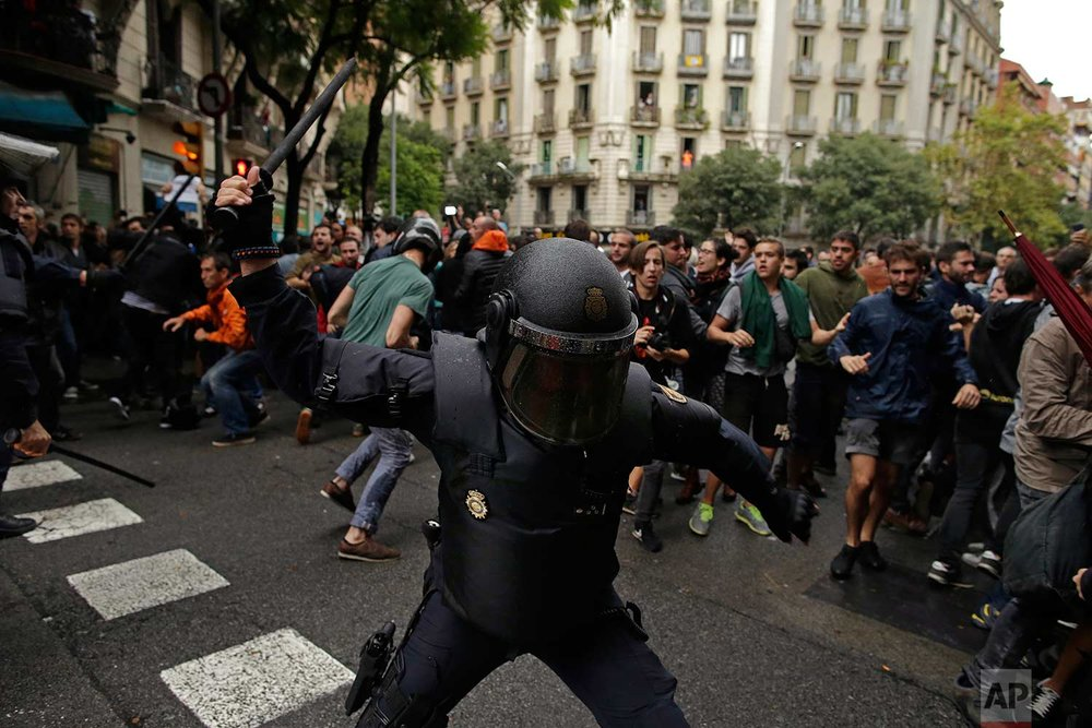 In this Sunday, 1 Oct. 2017 photo, Spanish riot police swings a club against would-be voters near a school assigned to be a polling station by the Catalan government in Barcelona, Spain. Spanish riot police have forcefully removed a few hundred would-be voters from several polling stations in Barcelona. (AP Photo/Manu Fernandez)