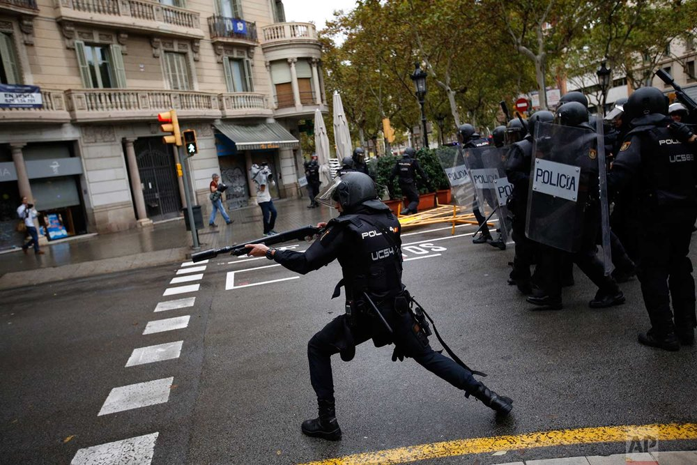 In this Sunday, 1 Oct. 2017 photo, Spanish riot police shoots rubber bullet straight to people trying to reach a voting site at a school assigned to be a polling station by the Catalan government in Barcelona, Spain. (AP Photo/Emilio Morenatti)