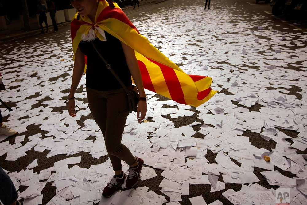 In this Tuesday Oct. 3, 2017 photo, a woman wearing an estelada or independence flag walks a long a street covered with referendum ballots threw by pro-independence demonstrators, during a rally in front of the Spanish Partido Popular ruling party headquarters in Barcelona, Spain. Labor unions and grassroots pro-independence groups are urging workers to hold partial or full-day strikes throughout Catalonia to protest alleged brutality by police during a referendum on the region's secession from Spain that left hundreds of people injured. (AP Photo/Emilio Morenatti)