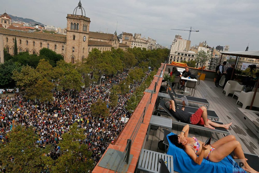 In this Tuesday Oct. 3, 2017 photo, a couple, tourists from Switzerland, sunbath at a terrace overlooking Universitat square as demonstrators gather in protest in downtown Barcelona, Spain. Labor unions and grassroots pro-independence groups are urging workers to hold partial or full-day strikes and demonstrations throughout Catalonia to protest alleged brutality by police during a referendum on the region's secession from Spain that left hundreds of people injured. (AP Photo/Enric Marti)
