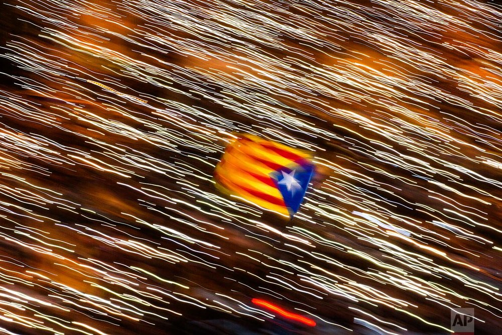 In this Saturday, Nov 11, 2017 photo, an independence flag is waved as demonstrators take part at a protest calling for the release of Catalan jailed politicians, in Barcelona, Spain. Eight members of the now-defunct Catalan government remain jailed in a related rebellion case. Former regional president Carles Puigdemont and four other ex-cabinet members fled to Belgium where they are fighting extradition. (AP Photo/Emilio Morenatti)