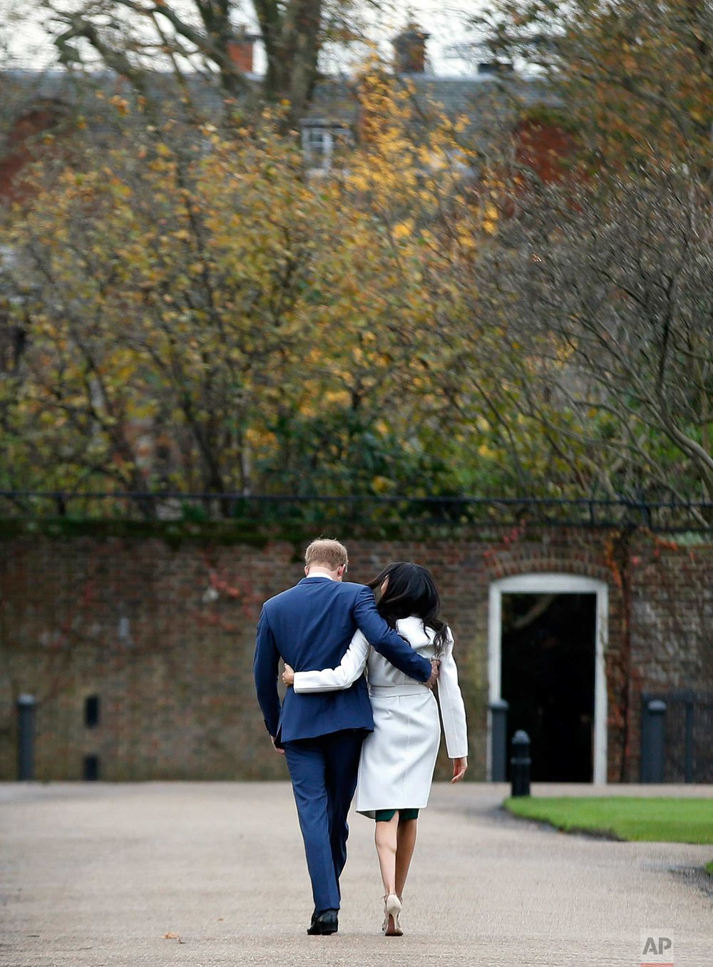In this Monday Nov. 27, 2017 photo, Britain's Prince Harry and Meghan Markle walk away after posing for the media in the grounds of Kensington Palace in London. It was announced Monday that Prince Harry, fifth in line for the British throne, will marry American actress Meghan Markle in the spring, confirming months of rumors. (AP Photo/Alastair Grant)