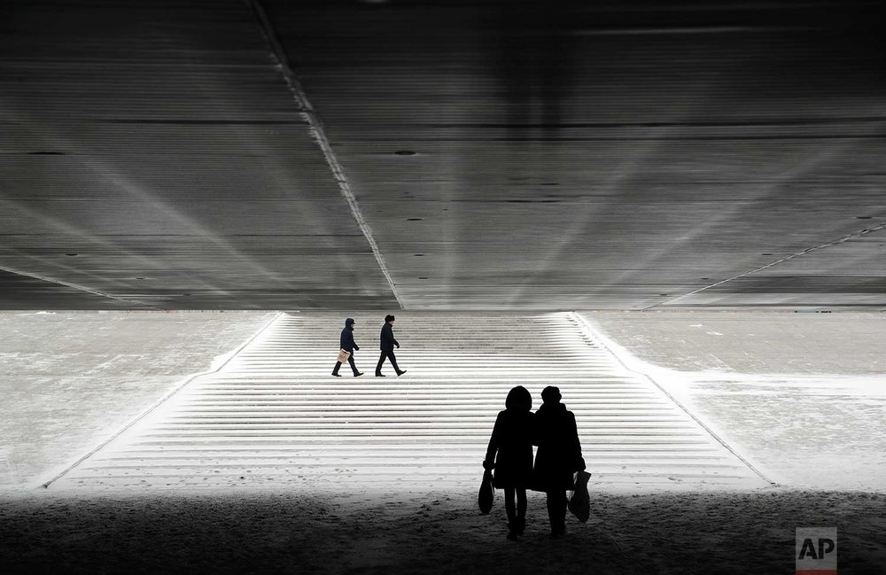 In this Wednesday, Jan. 25, 2017 photo, people walk through an underpass in Astana, Kazakhstan. The Kazakh capital was hit by a heavy gale and a snowfall with a temperature of - 6 C (F 21). (AP Photo/Sergei Grits)
