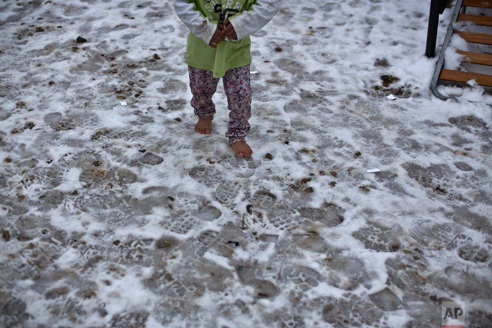 "In this Wednesday, Jan. 11, 2017 photo, a Syrian refugee child walks barefoot on frozen ground at the refugee camp of Ritsona about 86 kilometers (53 miles) north of Athens. The European Commission said conditions for refugees on islands and other camps where they are housed in tents despite severe cold weather, is ""untenable."" (AP Photo/Muhammed Muheisen)"