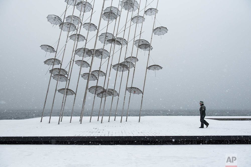 "In this Tuesday, Jan. 10, 2017 photo, a woman walks past ""Umbrellas"" sculpture, by George Zongolopoulos, at the seafront of the northern Greek city of Thessaloniki. Snow closed hundreds of schools in the country, as added pressure on the government to speed up winter preparations for thousands of refugees living in camps around the country. (AP Photo/Giannis Papanikos)"