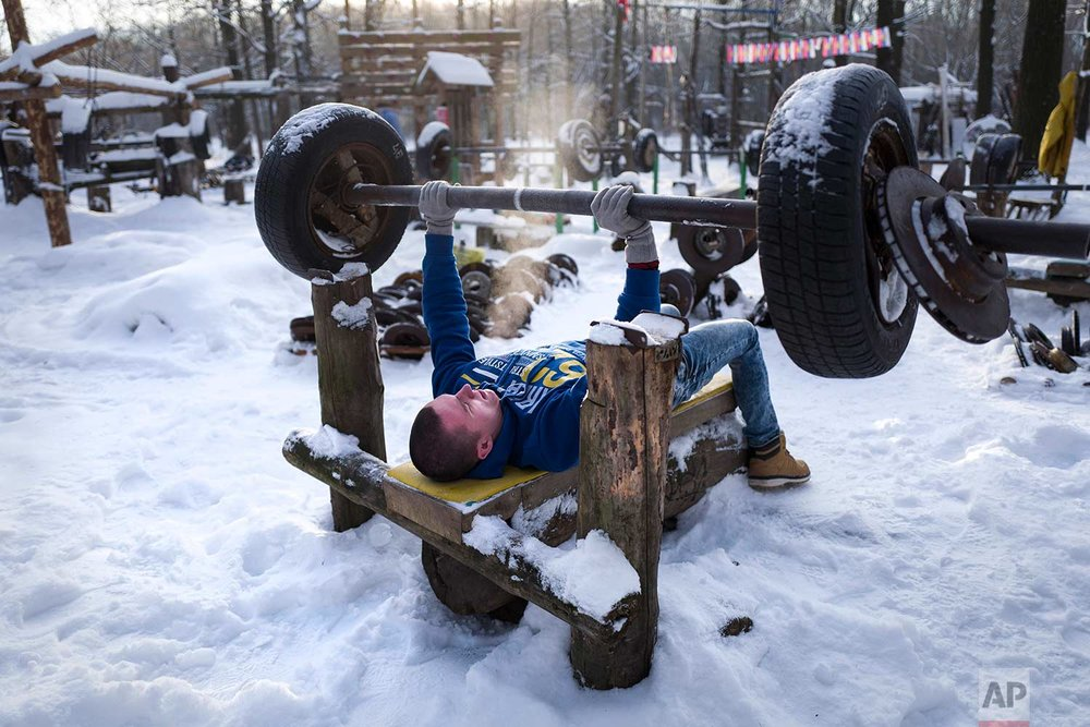 In this Thursday, Jan. 26, 2017 photo, a man trains in the outdoor gym in Timiryazevsky Park in Moscow, Russia. The morning temperature in Moscow is roughly minus -18 degrees Celsius (-0.4 Fahrenheit). (AP Photo/Alexander Zemlianichenko)