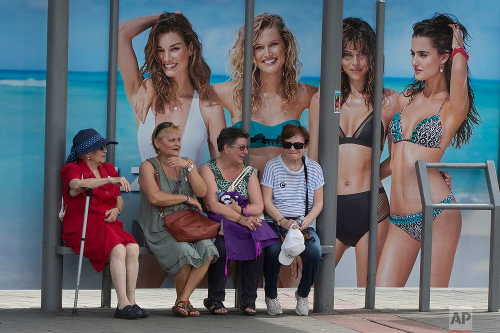 In this Saturday, May 27, 2017 photo, four women wait at a bus stop in front of an advertising poster for swimwear and beach wear in Madrid, Spain. (AP Photo/Paul White)