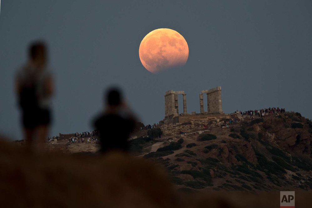 In this Monday, Aug. 7, 2017 photo, the August full moon rises above the 5th Century BC Temple of Poseidon at Cape Sounio, south of Athens. More than a hundred of Greece's ancient sites - but not the Acropolis in Athens - and museums were kept open until late Monday and concerts organized to allow visitors to enjoy the full moon, which is accompanied by a partial lunar eclipse. (AP Photo/Petros Giannakouris)