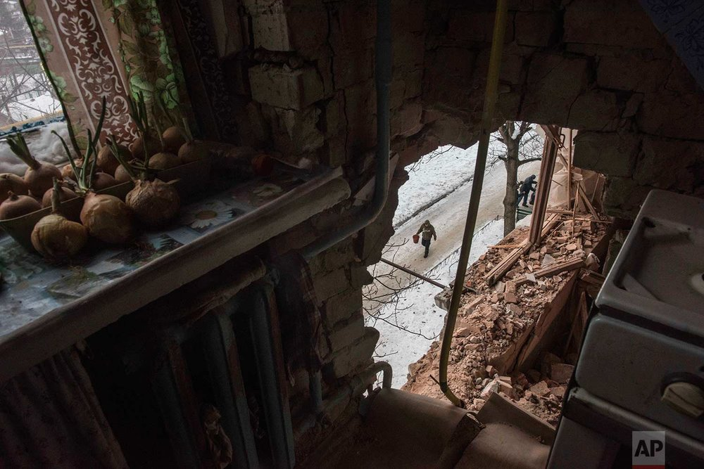 In this Saturday, Feb. 4, 2017 photo, a local resident walking in a street is seen through a hole in an apartment building damaged by shelling in Avdiivka, Ukraine. Fighting in eastern Ukraine sharply escalated this week. The Ukrainian command said Saturday that several soldiers were killed in the past day. (AP Photo/Evgeniy Maloletka)