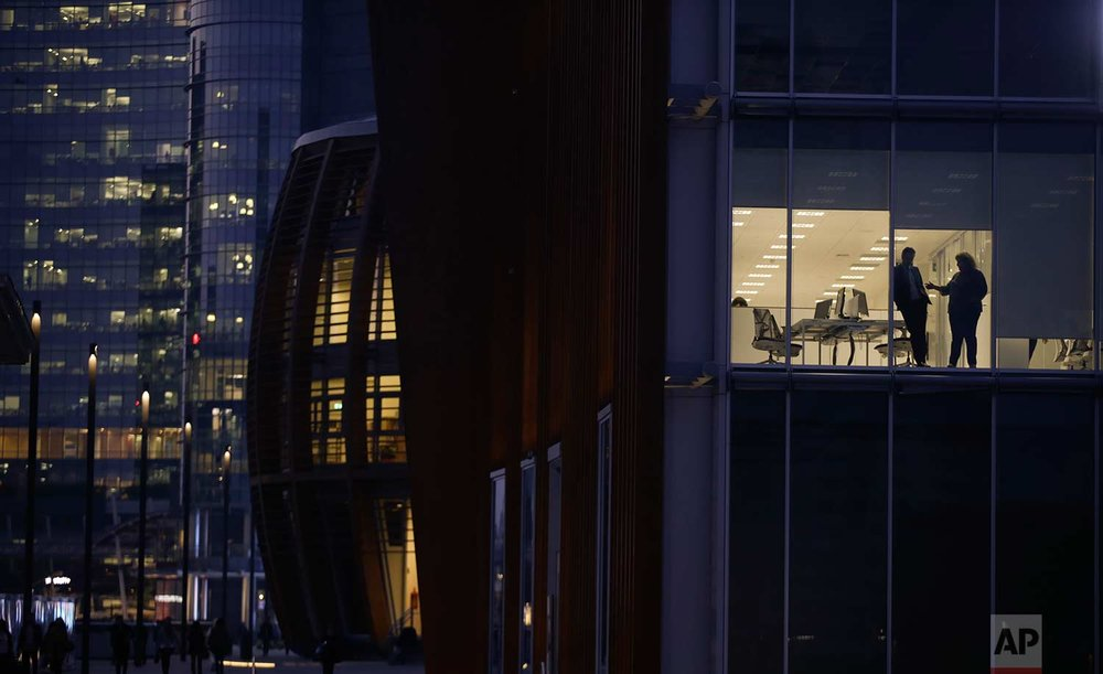 In this Wednesday, Oct. 18, 2017 photo, people are silhouetted behind the windows of an office, in Milan's Porta Nuova business district, Italy. (AP Photo/Luca Bruno)