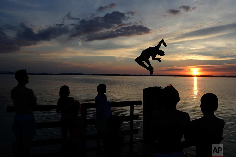 In this Saturday, July 22, 2017 photo, a man jumps into the water surrounded by his family at lake 'Chiemsee' in Chieming, Germany. (AP Photo/Matthias Schrader)