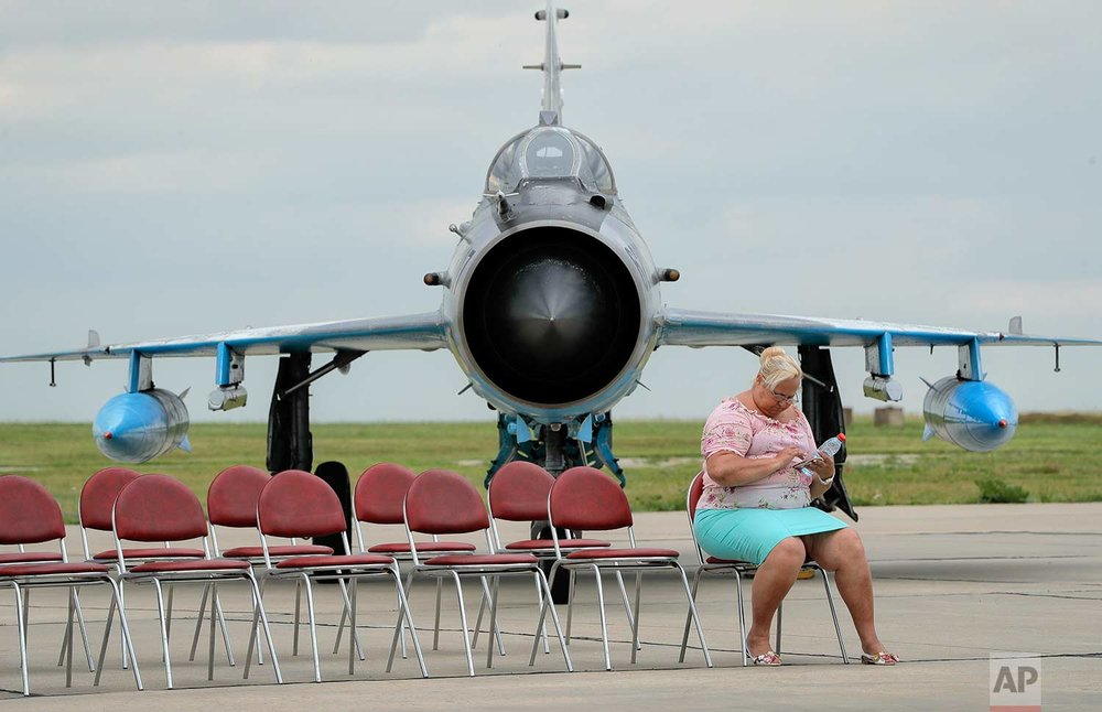"In this Wednesday, June 14, 2017 photo, a journalist, backdropped by a Soviet era built MIG 21 Romanian Air Force jet fighter operates a phone while waiting for Britain's defense minister Michael Fallon's arrival at the Mihail Kogalniceanu air base, Romania. Britain's defense minister praised Romanian and British pilots for protecting the Black Sea region from ""the persistent threat of Russian aggression,"" saying that Britain remains committed to NATO and the European security. (AP Photo/Vadim Ghirda)"