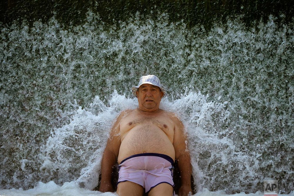 In this Sunday, Aug. 6, 2017 photo, a man cools off in a river in Buzau, Romania. A heatwave with an extreme temperatures of up to 42 Celsius (107.6 Fahrenheit) affected Romania over the past week and is expected to continue for the coming days in parts of the country. (AP Photo/Andreea Alexandru)