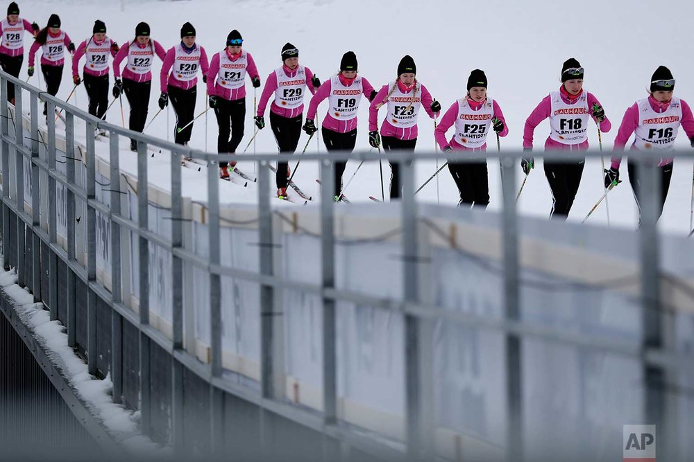 In this Wednesday, Feb. 22, 2017 photo, forerunners prepare the track prior to the women's 5 km cross-country individual classic qualification competition at the 2017 Nordic Skiing World Championships in Lahti, Finland. (AP Photo/Matthias Schrader)