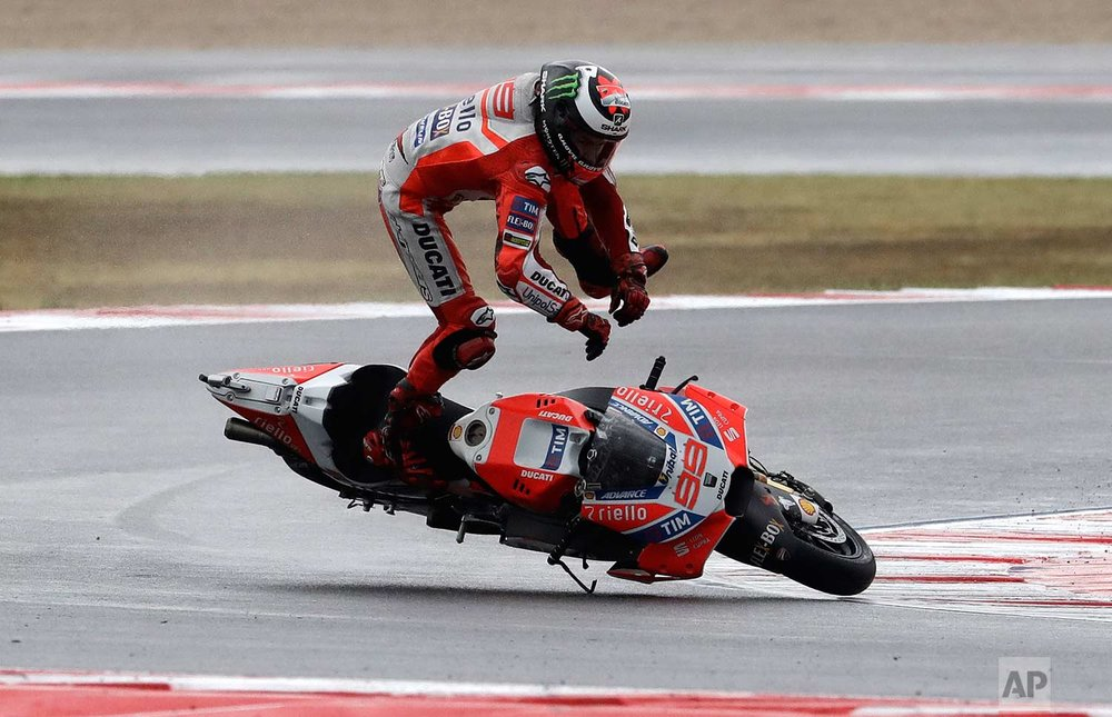 In this Sunday, Sept. 10, 2017 photo, Moto GP rider Jorge Lorenzo of Spain falls off his bike during the San Marino Motorcycle Grand Prix at the Misano circuit in Misano Adriatico, Italy. (AP Photo/Antonio Calanni)