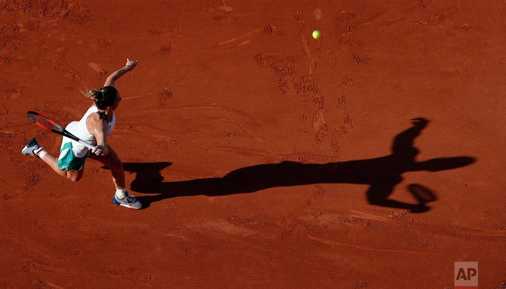 In this Tuesday, May 30, 2017 photo, Romania's Simona Halep reaches for the ball as she plays Slovakia's Jana Cepelova during their first round match of the French Open tennis tournament at the Roland Garros stadium in Paris. (AP Photo/Christophe Ena)