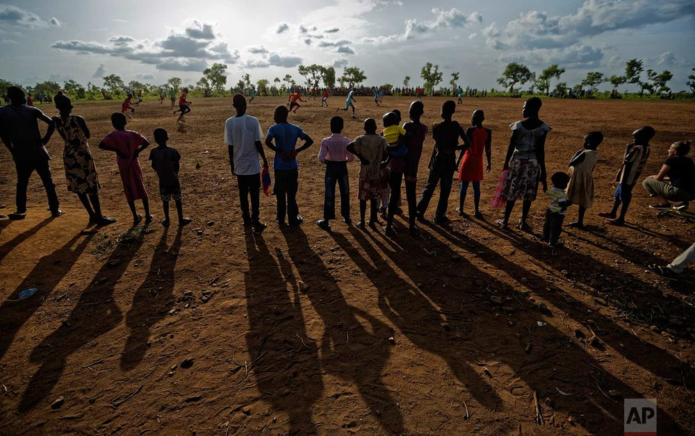 In this photo taken Sunday, June 4, 2017, South Sudanese refugees watch a match between refugee men's soccer teams, in the Bidi Bidi refugee settlement in northern Uganda. Soccer fields and inter-village competitions are found across the world's largest refugee settlement and even more are being created, underscoring the importance of sport in a community trying to forget the horrors of war with a rare source of entertainment in an otherwise dreary existence. (AP Photo/Ben Curtis)