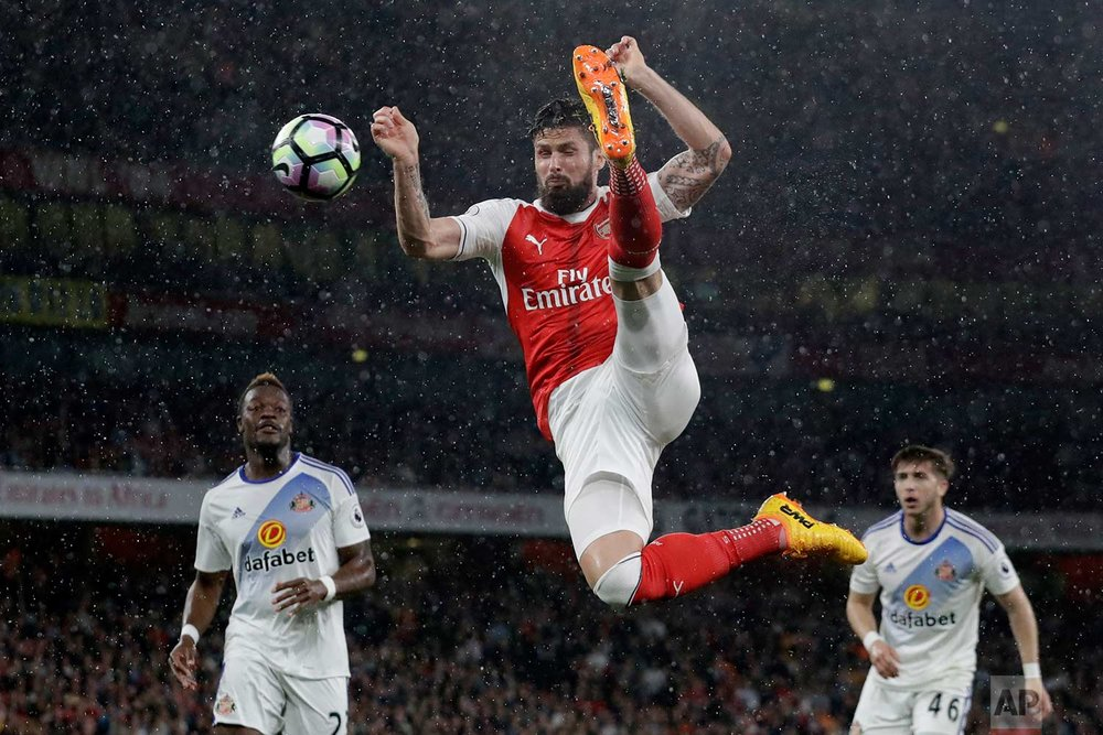 In this Tuesday, May 16, 2017 photo, Arsenal's Olivier Giroud hits the ball across goal, which Alexis Sanchez scored their side's second goal from during the English Premier League soccer match between Arsenal and Sunderland at the Emirates Stadium in London.  (AP Photo/Matt Dunham)