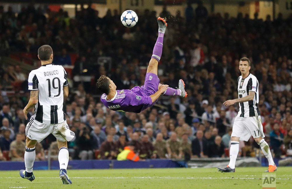 In this Saturday June 3, 2017 photo, Real Madrid's Cristiano Ronaldo connects with an overhead kick during the Champions League final soccer match between Juventus and Real Madrid at the Millennium stadium in Cardiff, Wales. (AP Photo/Frank Augstein)