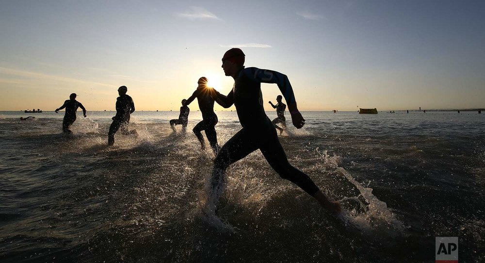 In this Saturday. Sept. 23, 2017 photo, athletes take the start of the swimming portion of an Ironman Triathlon competition, in Cervia, northern Italy. (AP Photo/Alessandro Trovati)