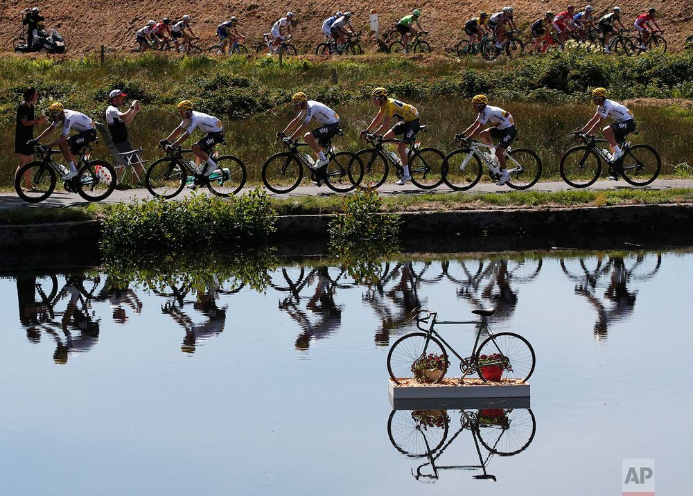 In this Wednesday, July 5, 2017 photo, Britain's Geraint Thomas, wearing the overall leader's yellow jersey, and new overall leader Britain's Chris Froome, left of Thomas, are reflected in a pond as they ride in the pack during the fifth stage of the Tour de France cycling race over 160.5 kilometers (99.7 miles) with start in Vittel and finish in La Planche des Belles Filles, France. (AP Photo/Christophe Ena)