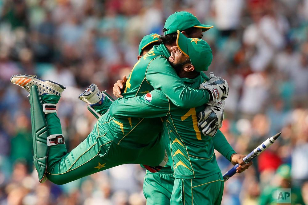 In this Sunday, June 18, 2017 photo, Pakistan's captain Sarfraz Ahmed, left, jumps over a teammate after they defeated India by 180 runs during the ICC Champions Trophy final at The Oval in London. (AP Photo/Kirsty Wigglesworth)
