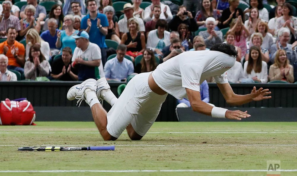 In this Saturday, July 15, 2017 photo, Brazil's Marcelo Melo falls to the ground with his shirt covering his face as he celebrates after he and his playing partner Poland's Lukasz Kubot, defeated Austria's Oliver Marach, and Croatia's Mate Pavic in the Men's Doubles final match on day twelve at the Wimbledon Tennis Championships in London. (AP Photo/Kirsty Wigglesworth)