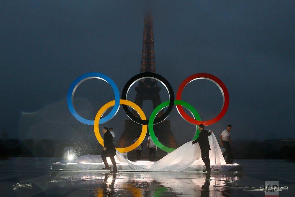 In this Wednesday, Sept. 13, 2017 photo, Paris officials unveil a display of the Olympic rings on Trocadero plaza that overlooks the Eiffel Tower, after the vote in Lima, Peru, awarding the 2024 Games to the French capital, in Paris, France. Paris will host the 2024 Summer Olympics and Los Angeles will stage the 2028 Games — a pre-determined conclusion that the International Olympic Committee has officially ratified in a history-making vote. (AP Photo/Francois Mori)