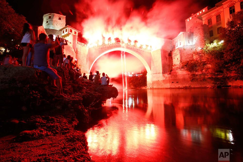 In this Sunday, July 30, 2017 photo, a Bosnian jumper, launches himself while holding burning torches, during traditional night jump from the Old Mostar Bridge, in Mostar, 140 kms south of Bosnian capital of Sarajevo. A total of 41 divers from Bosnia and neighbouring countries competed diving from the 25 meter (82 feet) high Old Mostar Bridge into the Neretva River. (AP Photo/Amel Emric)