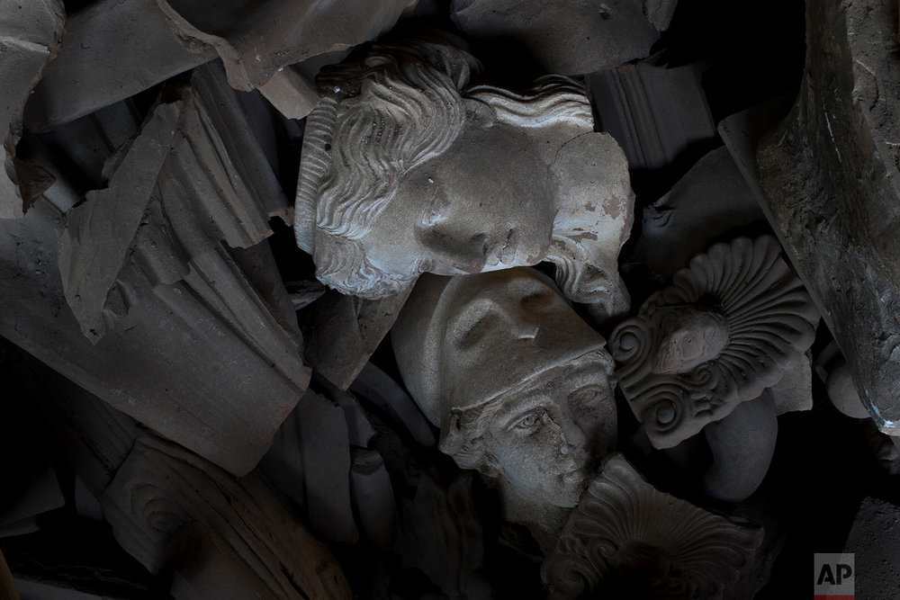 In this Friday, Nov. 20, 2017 photo, two terracotta busts of a Caryatid and the ancient Greek goddess of wisdom, Athena, are seen among other ceramic broken pieces in Haralambos Goumas' sculpture and ceramic workshop, in the Egaleo suburb of Athens. (AP Photo/Petros Giannakouris)
