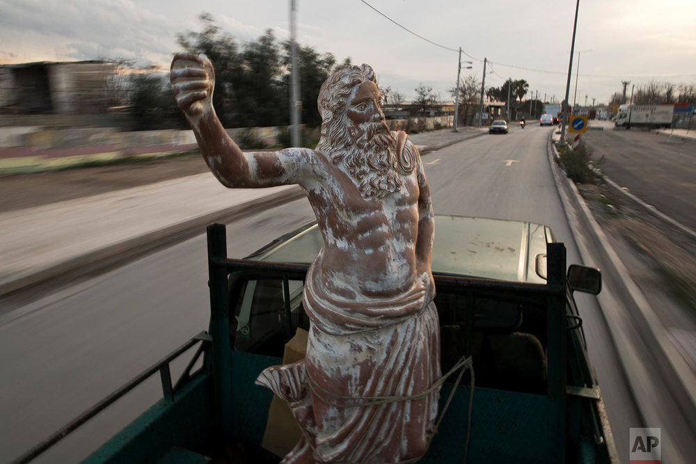 In this Tuesday, Dec 19, 2017 photo, a pickup track drives on a street of Athens carrying a terracotta statue of Zeus, chief among the ancient Greek gods, made by sculptor and ceramicist Haralambos Goumas. (AP Photo/Petros Giannakouris)
