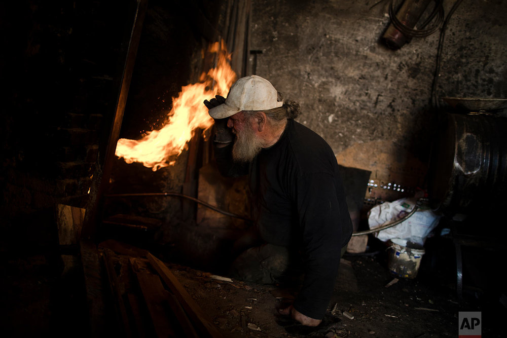 In this Friday, Nov. 20, 2017 photo, sculptor and ceramicist Haralambos Goumas looks into the fire as he tries to control the temperature of the furnace in his workshop in the Egaleo suburb of Athens. (AP Photo/Petros Giannakouris)