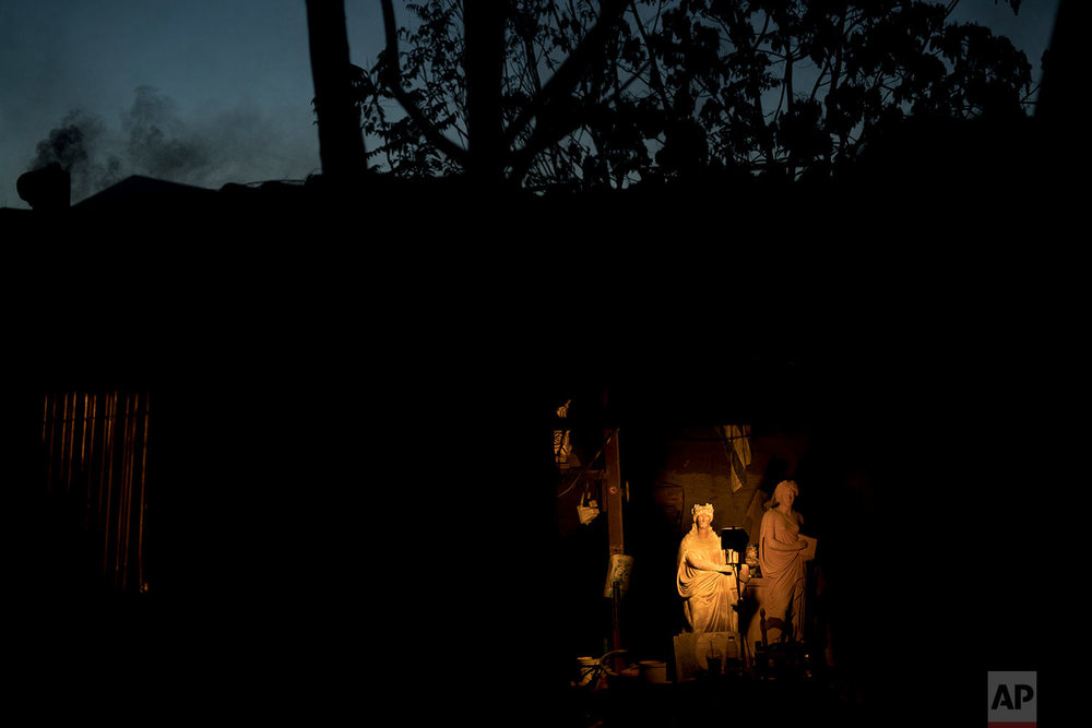 In this Friday, Nov. 20, 2017 photo, the terracotta statues of ancient Greek muses Erato, left, and Clio, stand in Haralambos Goumas' sculpture and ceramic workshop, in the Egaleo suburb of Athens. (AP Photo/Petros Giannakouris)