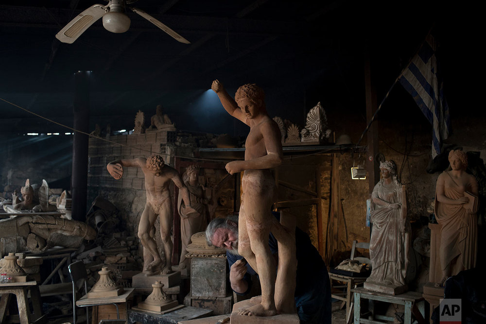 In this Tuesday, Dec. 19, 2017 photo, sculptor and ceramicist Haralambos Goumas works on a terracotta statue of Hermes, messenger of the ancient Greek gods, at his workshop in the Egaleo suburb of Athens. (AP Photo/Petros Giannakouris)