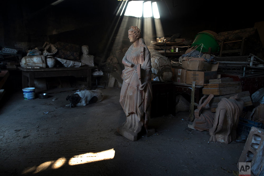 In this Friday, Nov. 20, 2017 photo, a dog lies next to a terracotta statue of Erato, one of the nine Muses of ancient Greek mythology, stands in Haralambos Goumas' ceramic workshop, in the Egaleo suburb of Athens. (AP Photo/Petros Giannakouris)