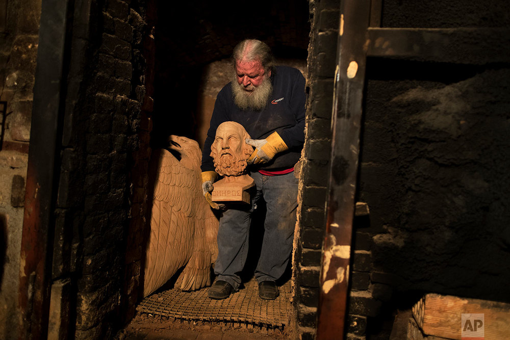 In this Thursday, Dec. 21, 2017 sculptor and ceramicist Haralambos Goumas carries out of a furnace the bust of Homer, whom Greek tradition named as the author of the Iliad and Odyssey epics, at his workshop in the Egaleo suburb of Athens. (AP Photo/Petros Giannakouris)