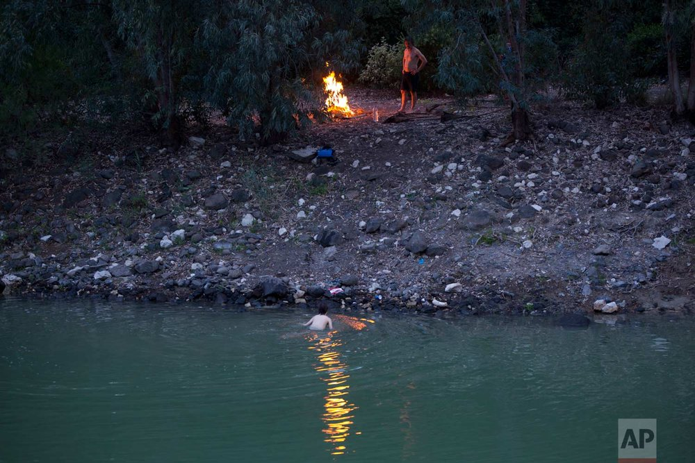 In this Tuesday, April 11, 2017 photo, Israelis camp out on the banks of the Jordan River near the northern Israeli Kibbutz of Kinneret. (AP Photo/Oded Balilty)
