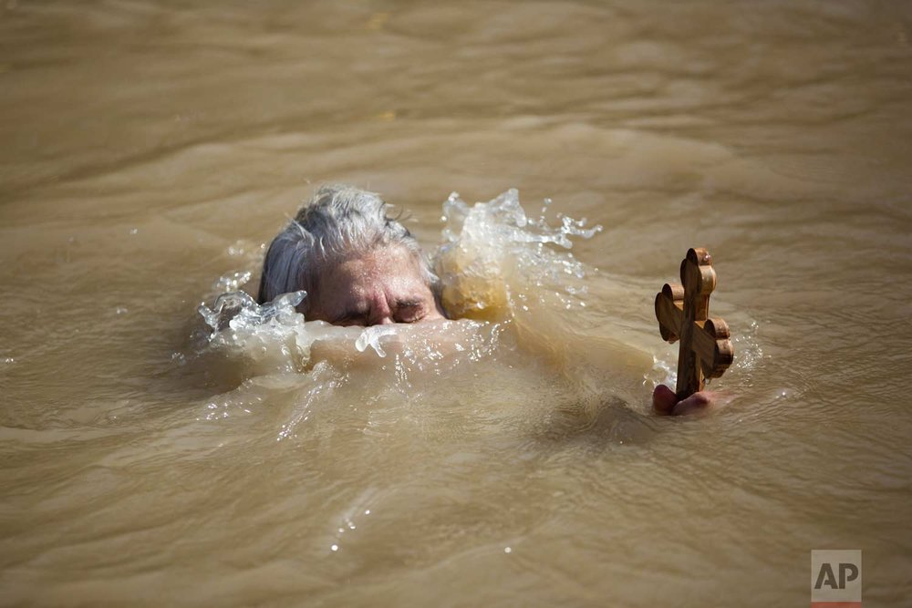 In this Wednesday, Jan. 18, 2017 photo, a Christian Orthodox pilgrim immerses herself into the waters of the Jordan River during a baptism ceremony as part of the Orthodox Feast of the Epiphany at Qasr el Yahud, the spot where John the Baptist is said to have baptized Jesus, near the West Bank town of Jericho. (AP Photo/Oded Balilty)