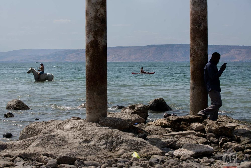 In this Sept. 23, 2017 photo, people enjoy the Sea of Galilee near the northern Israeli Kibbutz of Ein Gev. (AP Photo/Oded Balilty)