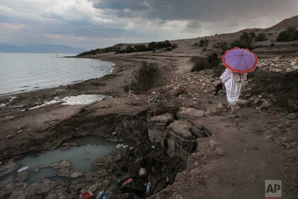 In this April 2, 2017 photo, a woman walks next to sinkholes along the Dead Sea shore near the Israeli Kibbutz of Ein Gedi. (AP Photo/Oded Balilty)