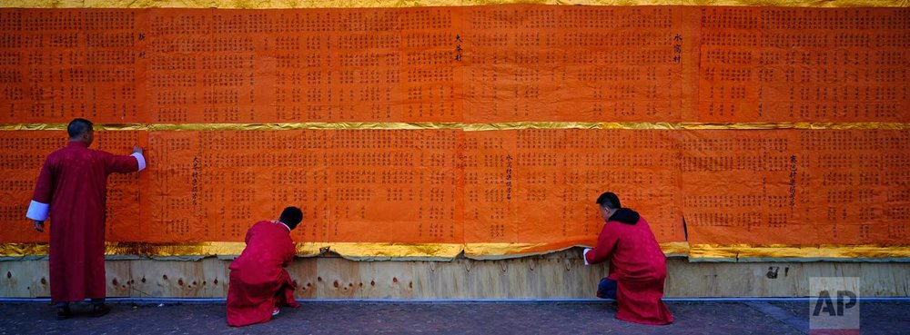 In this Dec. 10, 2017 photo, villagers try to take off a huge donation list to burn during the Tai Ping Ching Jiu festival at Lam Tsuen village in Hong Kong. (AP Photo/Vincent Yu)