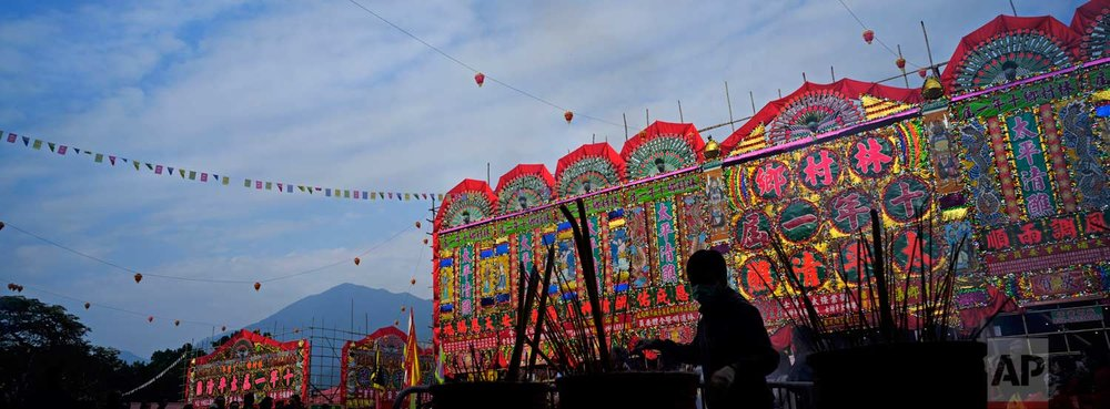 In this Dec. 10, 2017 photo, a villager burns incense in front of a huge bamboo theater with traditional decorations during the Tai Ping Ching Jiu festival at Lam Tsuen village in Hong Kong. (AP Photo/Vincent Yu)
