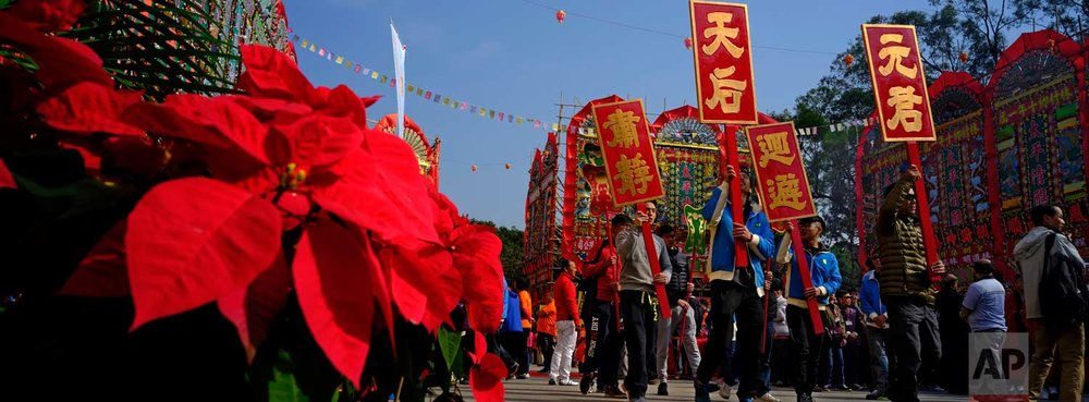 In this Dec. 10, 2017 photo, villagers raise wooden signs as they march past some Christmas flowers in front of a huge bamboo theater with traditional decorations during the Tai Ping Ching Jiu festival at Lam Tsuen village in Hong Kong. (AP Photo/Vincent Yu)