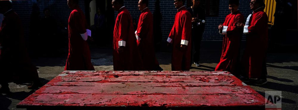 In this Dec. 10, 2017 photo, villagers walk past a table during a ceremony at the Tai Ping Ching Jiu festival at Lam Tsuen village in Hong Kong. (AP Photo/Vincent Yu)