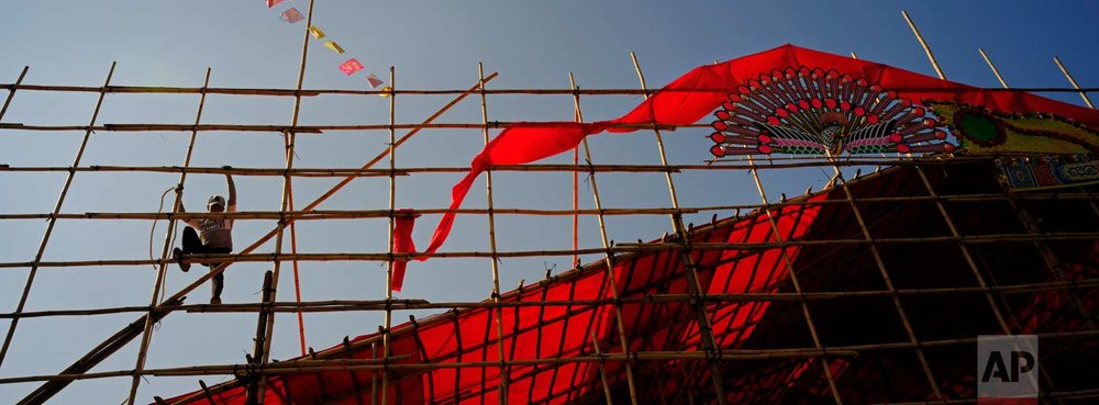 In this Dec. 19, 2017 photo, a worker climbs up a huge bamboo theater during demolition after the Tai Ping Ching Jiu festival at Lam Tsuen village in Hong Kong. (AP Photo/Vincent Yu)