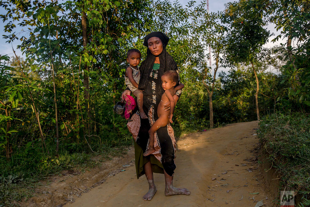 A Rohingya Muslim woman Zahida Banoo holds her son Mohammad Noor, left, and daughter Shah Heer as she poses for a photograph on the way to her shelter in Kutupalong refugee camp, Bangladesh, Friday, Sept. 15, 2017. With Rohingya refugees still flooding across the border from Myanmar, those packed into camps and makeshift settlements in Bangladesh were becoming desperate for scant basic resources as hunger and illness soared. (AP Photo/Dar Yasin)
