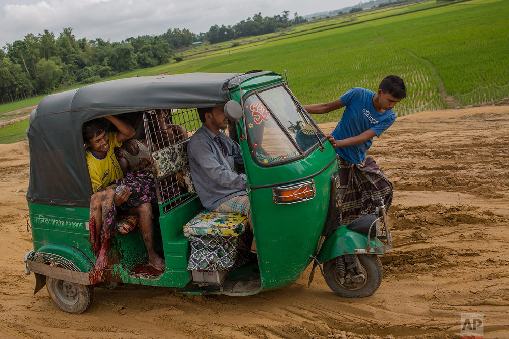 An injured Rohingya Muslim woman and her relatives rush to a hospital on an autorickshaw, near Kutupalong, Bangladesh, on Sept. 4, 2017. While crossing into Bangladesh, the elderly woman stepped on a land mind that blew off her right leg, witnesses said. Myanmar's military has been accused of planting land mines in the path of Rohingya Muslims fleeing violence in its western Rakhine state. (AP Photo/Bernat Armangue)