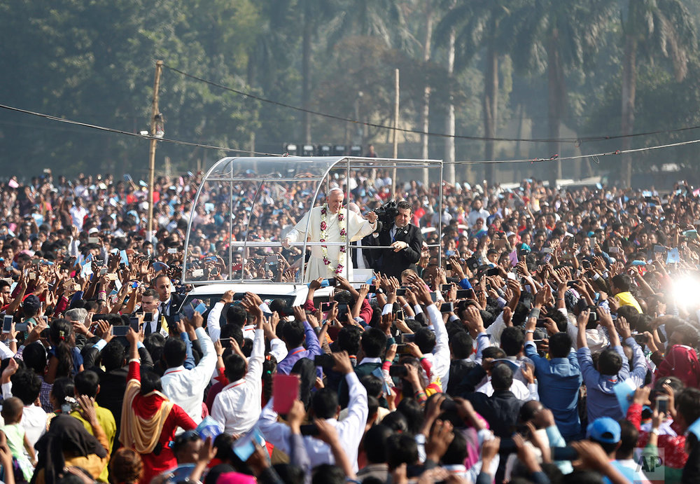 Pope Francis waves to faithful as he arrives arrives to celebrate mass and the ordination of new priests in Dhaka, Bangladesh, Friday, Dec. 1, 2017. Pope Francis ordained 16 priests during a Mass in Bangladesh on Friday, the start of a busy day that will bring him face-to-face with Rohingya Muslim refugees from Myanmar and the reality of Islamic extremism in South Asia. (AP Photo/Aijaz Rahi)