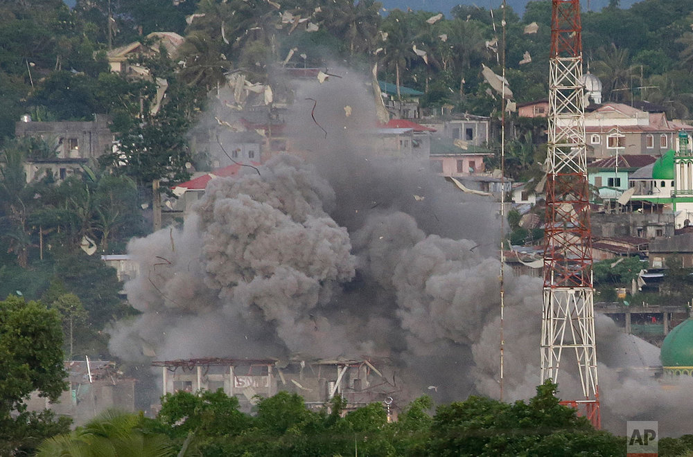 "Debris fly as Philippine Air Force fighter jets bomb suspected positions of Muslim militants as fighting continues in Marawi city, southern Philippines Friday, June 9, 2017. It's unclear how many people remain trapped in Marawi as government troops battle Muslim militants led by the so-called ""Maute"" group but army officers have put the figure this week at anywhere from 150 to 1,000. (AP Photo/Aaron Favila)"