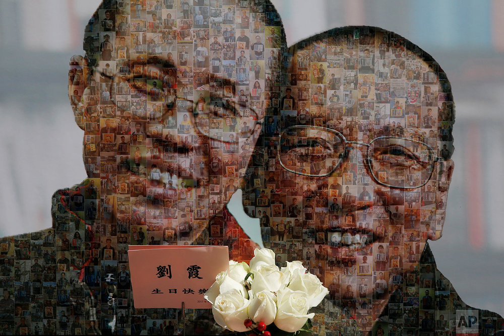 A poster featuring a image of jailed Chinese Nobel Peace laureate Liu Xiaobo and his detained wife Liu Xia, which is composed by photos of their supporters  are displayed during a demonstration in Hong Kong, Saturday, April 1, 2017 as they send a blessings for Liu Xia's birthday. The protesters demanded to release Liu Xiaobo and Liu Xia. (AP Photo/Kin Cheung)